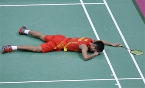 China's Lin Dan lies on the ground after a hard fought victory over Japan's Sho Sasaki, unseen, at a men's singles badminton quarterfinal match of the 2012 Summer Olympics, Thursday, Aug. 2, 2012, in London. (AP Photo/Saurabh Das)